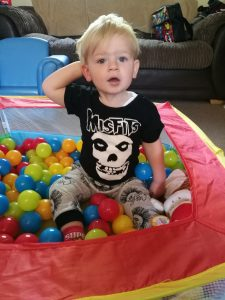 My Rocking Kids - Little boy sitting in a ball pall in black t-shirt with misfits and a skull in white