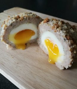 Homemade Scotch Eggs - On a chopping board, sliced in half with the middle oozing out
