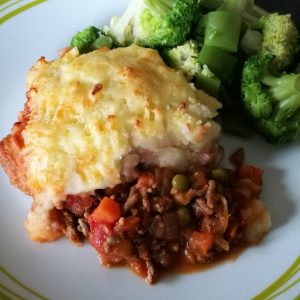 Cottage Pie - A plate with a heap of cottage pie and some green veggies next to it.