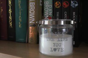 "Unique Things About Me - A white candle in a glass jar woth the words ""Live the life you love"" written in silver with books behind it."