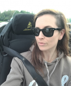 Unique Things About Me - Carly sitting in a car seat wearing black wayfarers. A bull and Lamborghini are sewn into the headrest of the seat