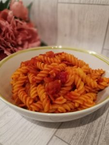 Pasta Amatriciana - A bowl of tomato sauce covered pasta with bits of bacon scattered throughout