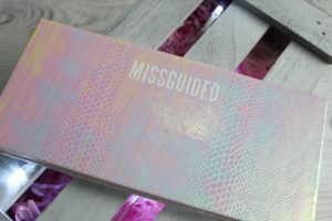 January Makeup Favourites - A rectangle package resting on a grey slatted wood background.The rectangle palette is a pink/blue holographic snakeskin with MISSGUIDED written along the top edge.