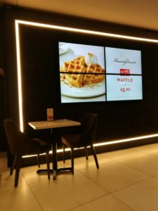 Heavenly Desserts Colchester - A black wall with a white light framing the edge and 4 TV screens in the middle with one big picture of waffles showing on them and a small table and 2 chairs to the left