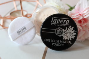 Lavera Natural Makeup - A black lid, the open pot of powder and a powder applicator stood on their side against copper candle holder and flowers