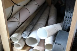 Living With A Blogger - sample rolls of wallpaper on top of each other under a small desk.
