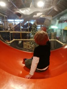 Soft Play Mum Guilt - Toddler sat in an orange and plastic bubble overlooking soft play equipment