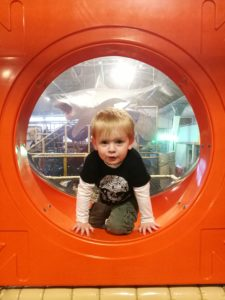 Soft Play Mum Guilt - Toddler climbing out of an orange plastic hole