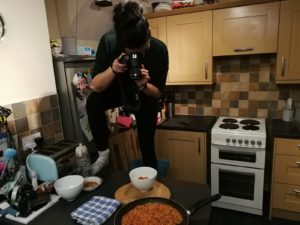 Living With A Blogger - Carly half standing on a kitchen counter with a DSLR taking pictures from above of a bowl and a pan of food.