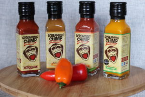 Screaming Chimp Chilli Sauce - 4 rectangular bottles in a row, stood on a wooden board with 2 small peppers in front of them.