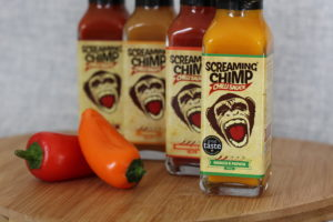 Screaming Chimp - 4 sauce bottles lined up behind each other on a wooden board