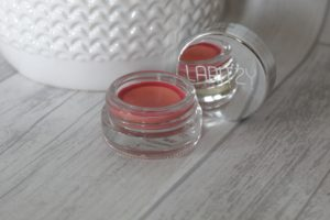 March 19 Glossybox - A small glass pot with shimmery brown creme inside and a mirrored lid standing up behind it.