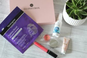 March 19 Glossybox - The contents of the box scattered across a white, wood with a succulent in the right hand corner.