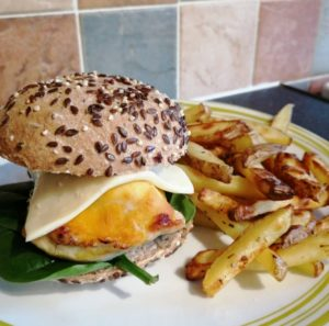 Screaming Chimp - A yellowish chicken breast in a seeded bun with some lettuce on the bottom and a slice of plastic cheese on top of the chicken. A portion of fries is next to the burger.