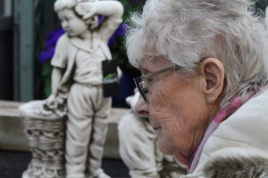 Loneliness in the elderly - a close up picture of an elderly lady's face with a statue of a boy in the background