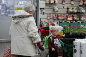 Loneliness in the elderly - A small boy in a dark red top and an elderly lady in a cream coat following him.