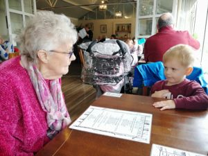 Loneliness in the elderly - An elderly lady and toddler boy sat at a table