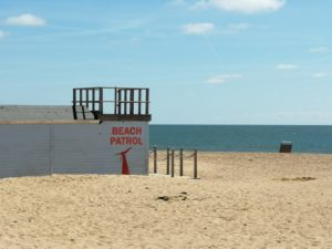 """Getting the perfect beach body - A blue hut on the sand with """"Beach Patrol"""" written on the side overlooking the sea"""