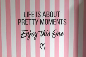 "A pink and white striped background with the words ""Life is about pretty moments. Enjoy this one"""