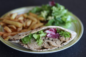 Healthy Doner Kebab - Sliced meat and lettuce leaves inside a pitta bread, on a plate with chips and more lettuce.