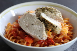 Herby Chicken with Sundried Tomato Pasta - a bowl of red pasta with clices of chicken laying on top