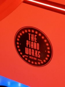 The Piano Works logo written in black on a bright red wall