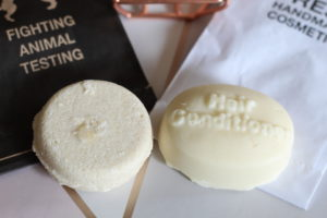 Lush Hair Care bars - two creamy coloured bars laying on their paper packaging