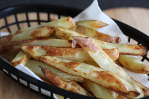 Rosemary and garlic baked fries - a black basket filled with chips.