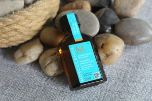 July 19 Glossybox - a brown bottle of hair oil with a turquoise label laying on rocks