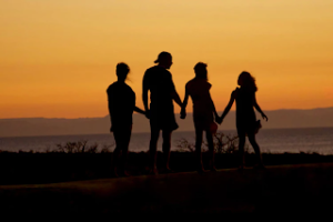 Tough times as a parent - silhouette of a family against a sunset