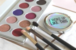 "5 beauty tips I would give to my daughter - an eyeshadow palette open with 3 brushes perched on the edge and a compact with ""I woke up like this"" written on the top."