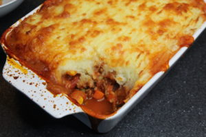 Cottage Pie - A white dish with splatters all over the sides filled with cottage pie but a spoonful has already gone