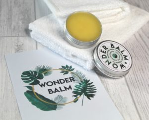 Wonder Balm - 2 white face cloths with the open tin of balm sat on top. Next to it is a card with Wonder Balm and leaves circling the words