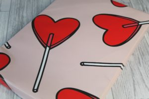 Wonder Balm - A rectangular, flat box wrapped in pink paper with large lollipop hearts