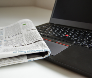 Remove negativity from your life - a newspaper folded and resting on top of an open laptop