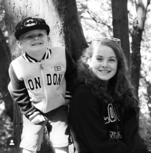 Things to do with the kids in January - A black and white picture of Carly's 2 children in the woods smilling at the camera