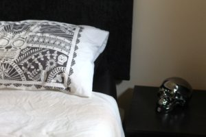 How to get a better night's sleep - white bedsheets and pillows against a black headboard with a black side-table and a black metallic skull sat on it.