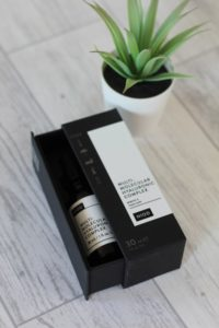 DECIEM - A small black box with a white label that's half open revealing a dark bottle with a white label on it