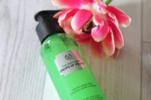 Form New Skincare Habits - A green bottle with a black pump on top lying next to a pink flower on a white wood background