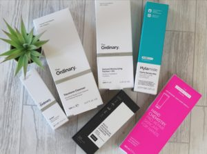 6 boxes of DECIEM products layed out on a white wood background with a small spiky plant to the left.