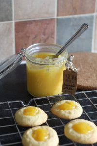 Gluten free, vegan thumbprint biscuits - a jar of bright yellow lemon curd and in front is 4 biscuits sat on a cooling rack