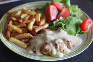 Gluten Free IKEA Style Meatballs covered with sauce on a plate with chips and salad