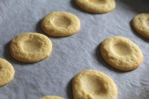 plain biscuits with little dents in the top ready for the lemon curd