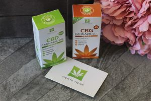 2 boxes, one green and white and the other brown and white stood up with a business card under the corner of one with Herts Hemp and a cannabis leaf logo on it