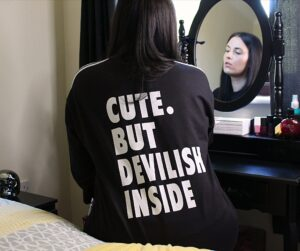 "Carly sat at a black dressing table with her back to the camera and you can see her reflection in the mirror. She's wearing the black and white tracksuit that has the words ""cute but devilish inside"" on it in white letters."