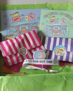 Inside the Sugar & Sloth Tiny Party Club box. 2 colourful postcards, a pink striped bag, a purple stripped bag, a badge and a bracelet