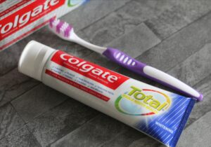 A tube of toothpaste lying next to a purple and white toothbrush