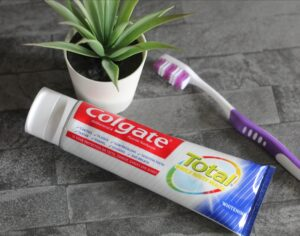 Fun ways of getting kids to look after their teeth - A tbe of Colgate toothpaste lying on a grey tiled background next to a purple and white toothbrush and a small potted plant