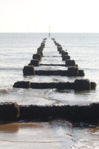 Sea Safety - a wooden groyne going out to sea. The water looks flat and grey