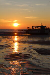 Sea Safety - a sunrise picture with a reflection of the sun in the sand and a silhouette of a boat beached on the sand.